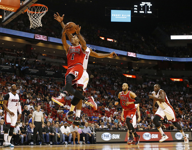 In this March 1, 2016 file photo, Chicago Bulls Derrick Rose (1) goes past Miami Heat's Amar'e Stoudemire (5) as he goes to the basket during the first half of an NBA basketball game  in Miami. (J ...
