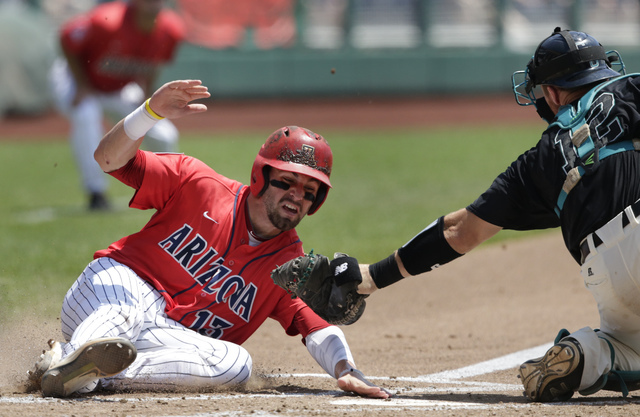 Arizona's Cody Ramer (13) is tagged out at home plate by Coastal Carolina catcher David Parrett (12) in the third inning in Game 3 of the NCAA College World Series baseball finals in Omaha, Neb.,  ...