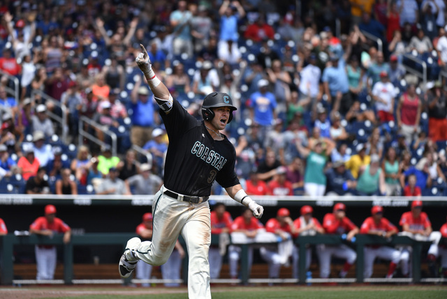 Coastal Carolina's G.K. Young celebrates his two-run home run against Arizona pitcher Bobby Dalbec in the  sixth inning in Game 3 of the NCAA College World Series baseball finals in Omaha, Neb., T ...