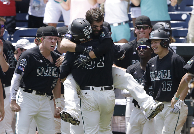Coastal Carolina's G.K. Young (37) is hugged by Anthony Marks after hitting a two-run home run against Arizona in the sixth inning in Game 3 of the NCAA College World Series baseball finals in Oma ...