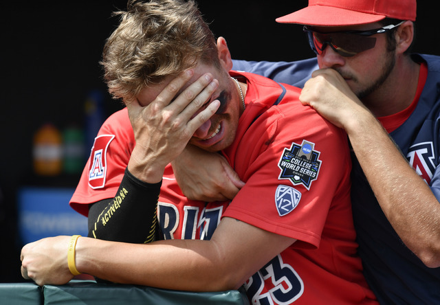Arizona's Zach Gibbons (23) is comforted by Ray McIntire after losing to Coastal Carolina 4-3 in Game 3 of the NCAA College World Series baseball finals in Omaha, Neb., Thursday, June 30, 2016. (T ...