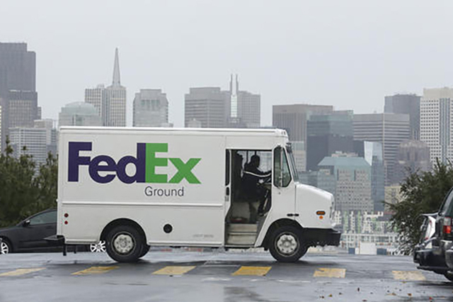 A FedEx truck drives past the skyline in San Francisco. Two giants, the U.S. government and FedEx, are set to do battle in a federal court over the explosive claim that the shipping company knowin ...