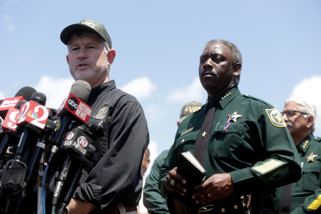 Nick Wiley, executive director of the Florida Fish and Wildlife Conservation Commission, alongside Orange County Sheriff Jerry L. Demings, speaks to the news media at the Disney Resort on Wednesda ...
