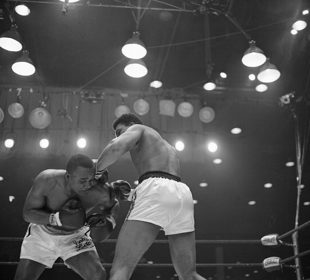 Muhammad Ali (Cassius Clay), right, lands both gloves on the left shoulder of Sonny Liston in an early of their scheduled 15-round heavyweight championship fight in Miami Beach, Florida on Feb. 25 ...