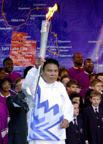 Boxing legend Muhammad Ali holds up the first Olympic torch lit from the cauldron in front of a map showing the torch's route during a ceremony at Centennial Olympic Park in Atlanta Tuesday, Dec.  ...