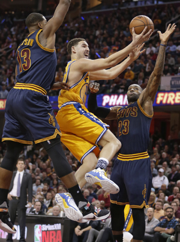 Golden State Warriors Klay Thompson, center, shoots around Cleveland Cavaliers' Tristan Thompson, left, from Canada, and Cleveland Cavaliers' LeBron James in the first half of an NBA basketball ga ...