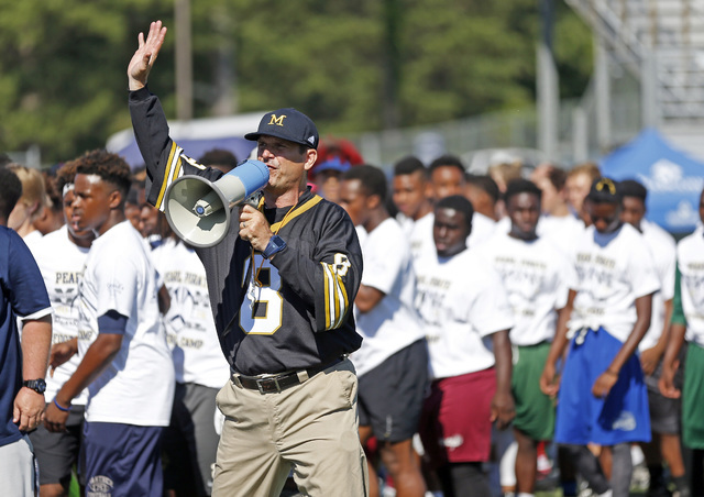 Michigan football coach Jim Harbaugh urges the more than 500 high school football players to listen to his explanation to a speed drill, Wednesday, June 8, 2016 at a Michigan Satellite Camp at Pea ...