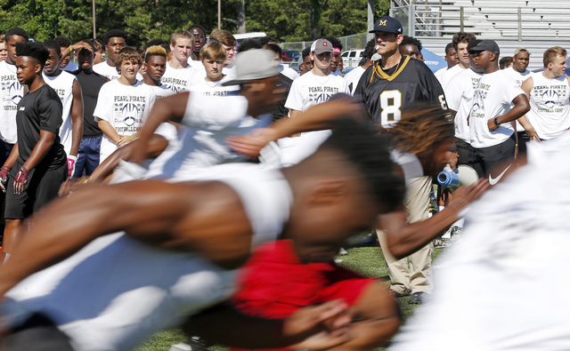 Michigan football coach Jim Harbaugh watches high school football players run a speed drill, Wednesday, June 8, 2016 at a Michigan Satellite Camp at Pearl High School in Pearl, Miss. (AP Photo/Rog ...