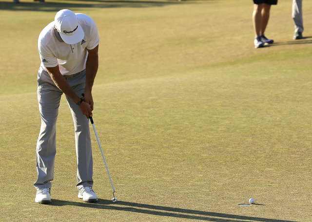 FILE - In this June 21, 2015, file photo, Dustin Johnson three-putts on the 18th hole during the final round of the U.S. Open golf tournament at Chambers Bay in University Place, Wash. Johnson los ...