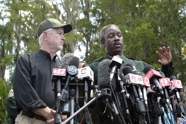 Nick Wiley, executive director of the Florida Fish & Wildlife Conservation Commission, left, and Orange County Sheriff Jerry Demings answer questions from reporters during a news conference We ...
