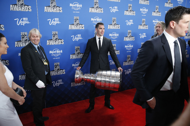 Pittsburgh Penguins' Pascal Dupuis holds up the Stanley Cup on the red carpet before the NHL Awards show Wednesday in Las Vegas. (AP Photo/John Locher)