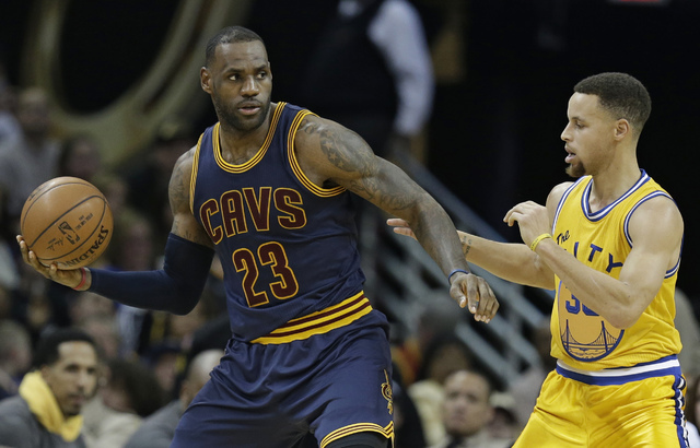 Cleveland Cavaliers' LeBron James, left,  drives past Golden State Warriors Stephen Curry in the second half of an NBA basketball game, Monday, Jan. 18, 2016, in Cleveland.  (Tony Dejak/AP)