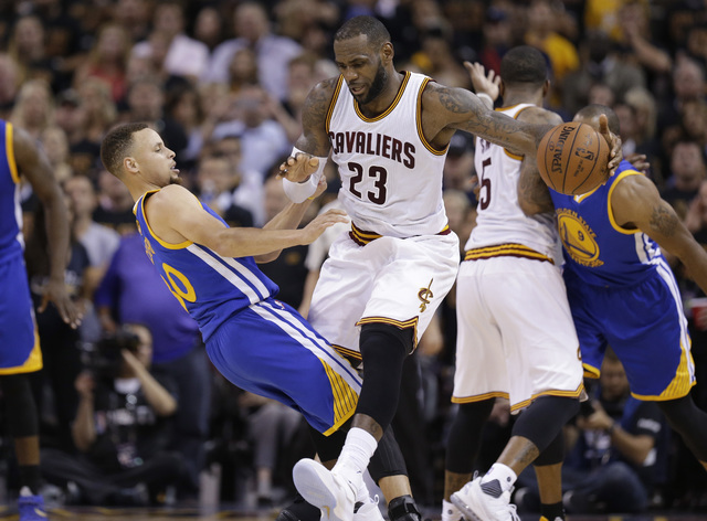 Cleveland Cavaliers forward LeBron James (23) and Golden State Warriors guard Stephen Curry (30) collide during the first half of Game 6 of basketball's NBA Finals in Cleveland, Thursday, June 16, ...