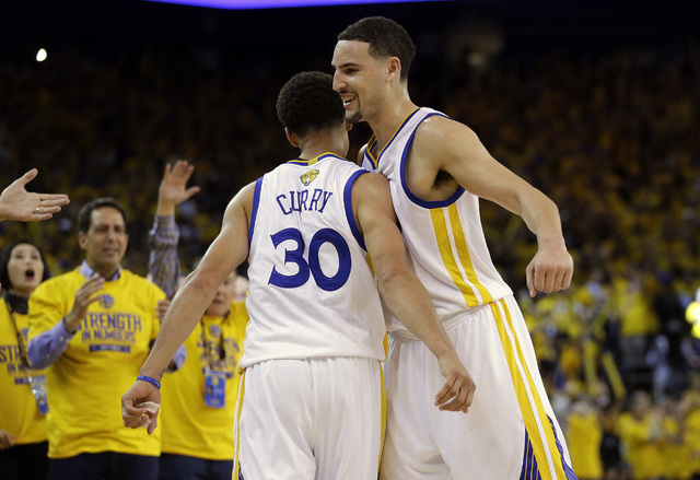 Golden State Warriors guard Stephen Curry (30) celebrates with guard Klay Thompson during the second half of Game 5 of the NBA Finals against the Cleveland Cavaliers in Oakland, Calif. on June 14, ...