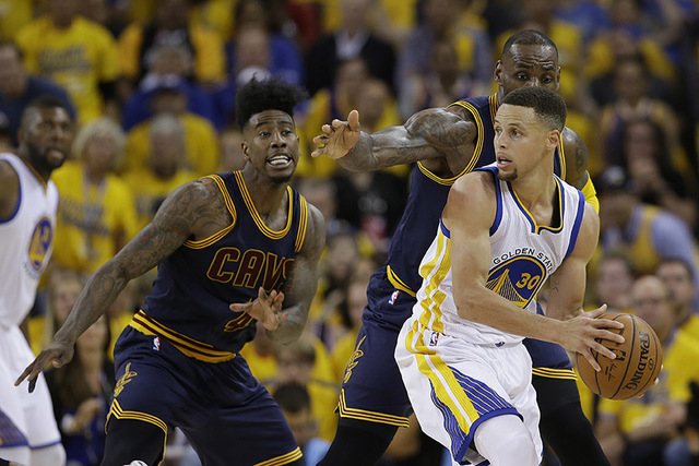 Golden State Warriors guard Stephen Curry (30) is guarded by Cleveland Cavaliers forward LeBron James and guard Iman Shumpert (4) during the second half of Game 1 of basketball's NBA Finals in Oak ...