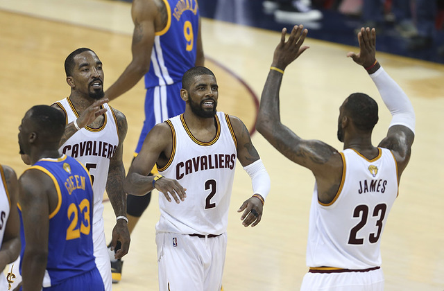 Cleveland Cavaliers forward LeBron James (23) celebrates with Kyrie Irving (2) and J.R. Smith (5) against the Golden State Warriors during the first half of Game 6 of basketball's NBA Finals in Cl ...