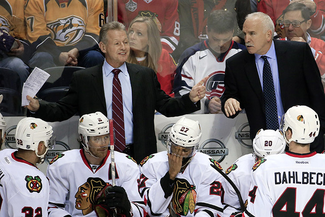 Joel Quenneville, right, and assistant coach Mike Kitchen, left, talk to their players in the second period of an NHL hockey game against the Nashville Predators, Saturday, Dec. 6, 2014, in Nashvi ...