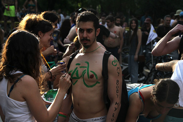 Protesters paint their bodies during a bicycle protest in the northern Greek city of Thessaloniki, on Friday, June 6, 2014. Hundreds people took part in the ride, many in makeup, wigs and strategi ...
