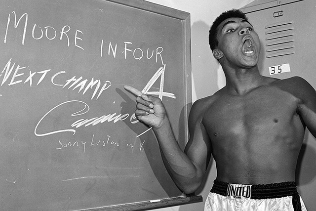 In this Nov. 15, 1962, file photo, young heavyweight boxer Cassius Clay, who later changed his name to Muhammad Ali,  points to a sign he wrote on a chalk board in his dressing room before his fig ...