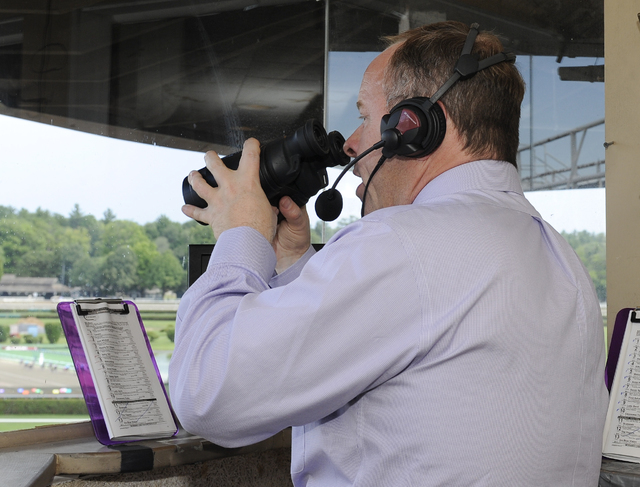 New York Racing Association track announcer Larry Collmus calls the sixth horse race on opening day of the season at Saratoga Race Course in Saratoga Springs, N.Y., Friday, July 24, 2015. (AP Phot ...