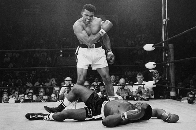 Heavyweight champion Muhammad Ali stands over fallen challenger Sonny Liston, shouting and gesturing shortly after dropping Liston with a short hard right to the jaw on May 25, 1965, in Lewiston,  ...