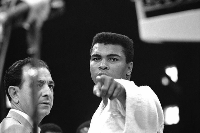 Heavyweight champion Muhammad Ali is momentarily displeased after weigh-in ceremony, May 25, 1965 in Lewiston, Maine, arena. Challenger Sonny Liston will be the object of Ali's more potent attenti ...