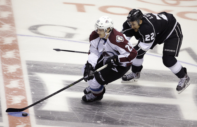 Colorado Avalanche center Nathan MacKinnon (29) skates by Los Angeles Kings center Trevor Lewis (22) during their NHL preseason hockey game, Oct. 4, 2014, in Las Vegas. Colorado won 3-2 in a shoot ...