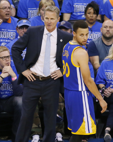 Golden State Warriors head coach Steve Kerr and guard Stephen Curry (30) watch action against the Oklahoma City Thunder during the first half in Game 6 of the NBA basketball Western Conference fin ...