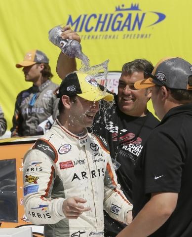 Chris Osborne, crew member for Erik Jones, pours a drink on Daniel Suarez in victory lane after Suarez won the NASCAR Xfinity series auto race at Michigan International Speedway, Saturday, June 11 ...