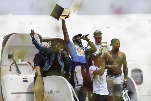 Cleveland Cavaliers' Lebron James, center, holds up the NBA Championship trophy alongside teammates Kyrie Irving, left, Kevin Love, rear right, J.R. Smith, right, and Tristan Thompson, front,   at ...