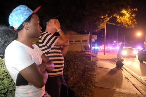 Jermaine Towns, left, and Brandon Shuford wait down the street from a shooting at Pulse nightclub in Orlando, Fla., Sunday, June 12, 2016, where 49 people were shot to death. Towns said his brothe ...