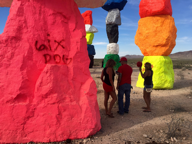 People stand in the shade of the towering rocks at the Seven Magic Mountains art project off Interstate 15 on Sunday, June 5, 2016.  (Natalie Bruzda/Las Vegas Review-Journal)
