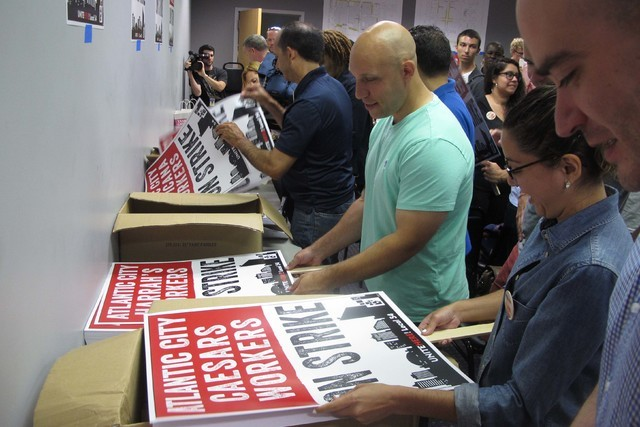 Union members assemble picket line signs as prepare for a strike against as many as five of the city's eight casinos in Atlantic City, N.J. on Wednesday June 29, 2016. (Wayne Parry/AP)