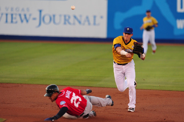 Las Vegas shortstop Gavin Cecchini turns a double play while Tacoma Rainiers base runner Ketel Marte slides into second base in the first inning of their minor league baseball game at Cashman Fiel ...