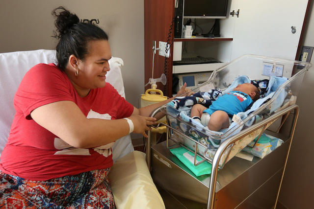 Gina Hilton reaches over to pick up her son Moses William Hilton, who fills his baby crib, at Hutchinson Regional Medical Center, in Hutchinson, Kan. Moses weighed over 14 pounds when he was born  ...