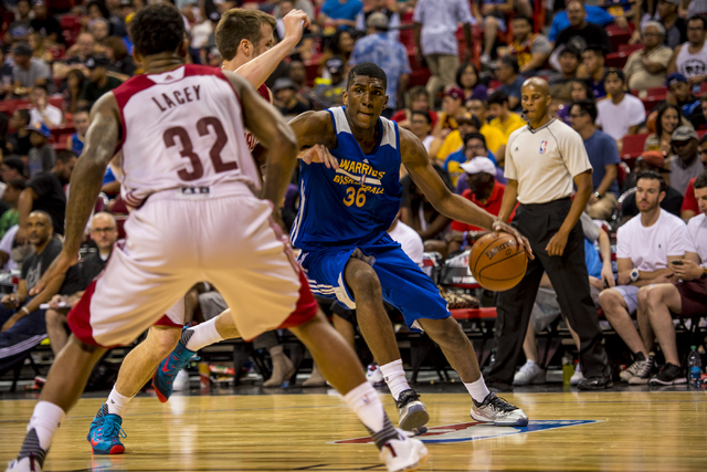 Kevon Looney (36) of the Golden State Warriors makes a move against John Shurma (24) and Trevor Lacey (32) of the Cleveland Cavaliers during the NBA Summer League at the Thomas & Mack Center i ...