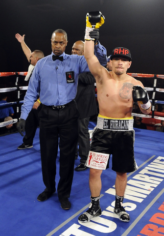 Referee Kenny Bales hoists the hand of Jesus Gutierrez after Guitierrez knocked out Pablo Becerra in the first round of their lightweight bout at the Tropicana Hotel Pavilion in Las Vegas Saturday ...