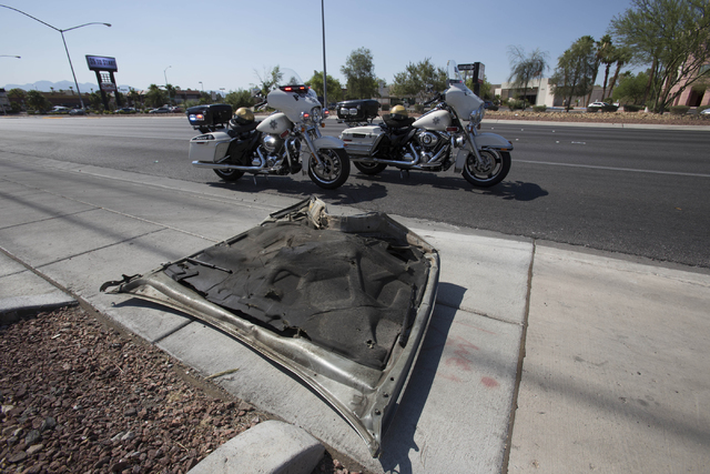 A wrecked hood of a car is seen on the sidewalk at the scene of a crash near the intersection of West Sahara Avenue and South Decatur Boulevard in Las Vegas on Saturday, June 25, 2016. Richard Bri ...
