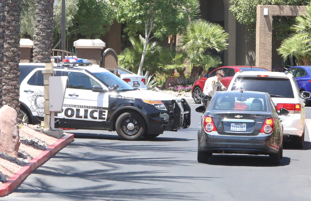 A Las Vegas police officer talks to residents outside a two-story apartment complex at 8000 Spring Mountain Road, near Buffalo Drive where one person died and two adults were displaced after a fir ...