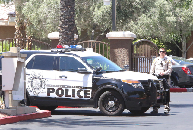 A Las Vegas police officer stands guard outside a two-story apartment complex at 8000 Spring Mountain Road, near Buffalo Drive where one person died and two adults were displaced after a fire on M ...