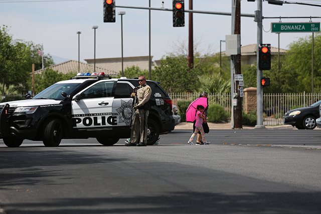 An officer stands on the perimeter of a seat area at the intersection of 28th street and Bonanza Road on Friday, June 10, 2016. Police are working to apprehend shooting suspects near the downtown  ...