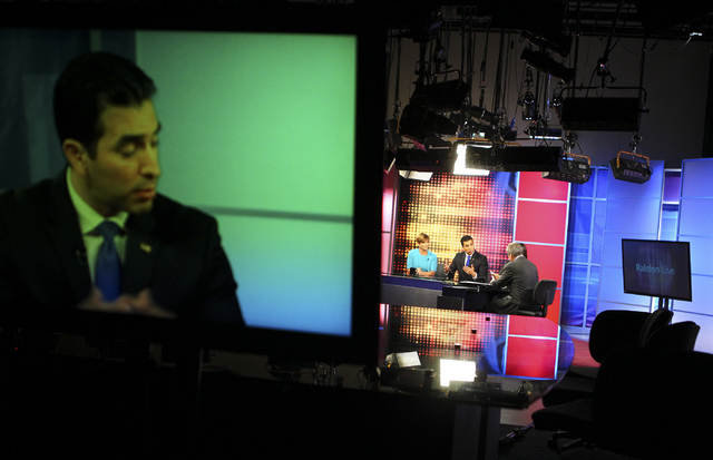 Democratic candidate for the 4th Congressional District,  State Sen. Ruben Kihuen, is shown on a monitor while debating with fellow candidates as Jon Ralston, right, moderates at Vegas PBS in Las  ...