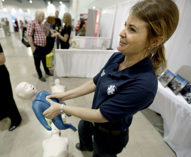Advance EMT Kelli Sonner with Guardian Elite  Medical Services demonstrates CPR during the Business Expo sponsored by Las Vegas Metro Chamber at Cashman Field on Wednesday, June 15, 2016.  Jeff Sc ...