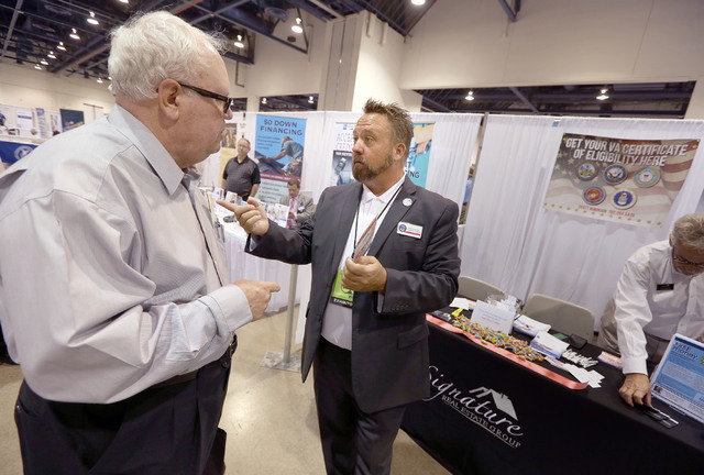 Scott Robinson, right, sales manager with Freedom Mortgage, talks to Grant Trauth about home loans during the Business Expo sponsored by Las Vegas Metro Chamber at Cashman Field on Wednesday, June ...
