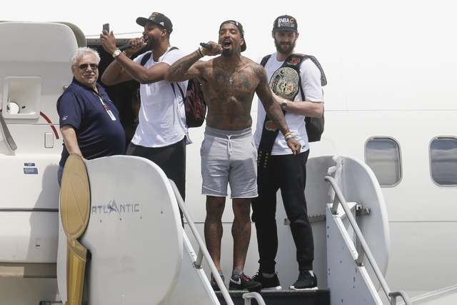 Cleveland Cavaliers' Tristan Thompson, second from left, J.R. Smith, center, and Kevin Love, right, celebrate as they arrive at the airport after winning Game 7 of basketball's NBA Finals against  ...