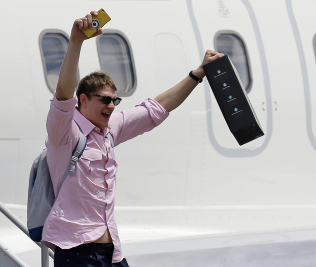 Cleveland Cavaliers' Timofey Mozgov, from Russia, raises his arms as he departs the airplane in Cleveland, Monday, June 20, 2016. The Cavaliers defeated Golden State in Game 7 of the NBA Finals on ...