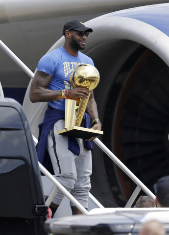 Cleveland Cavaliers' LeBron James carries The Larry O'Brien NBA Championship Trophy after arriving in Cleveland, Monday, June 20, 2016. (Tony Dejak/AP)