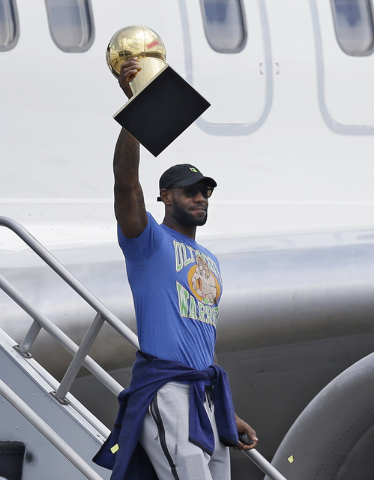 Cleveland Cavaliers' LeBron James raises the NBA Championship trophy after arriving at the airport, Monday, June 20, 2016, in Cleveland. (Tony Dejak/AP)