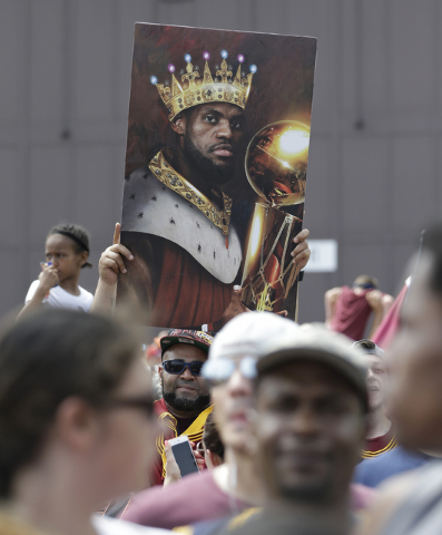 A man holds up a photo of Cleveland Cavaliers' LeBron James as he waits the arrival of the team in Cleveland, Monday, June 20, 2016. Lebron James came home with the trophy he promised, and the cha ...