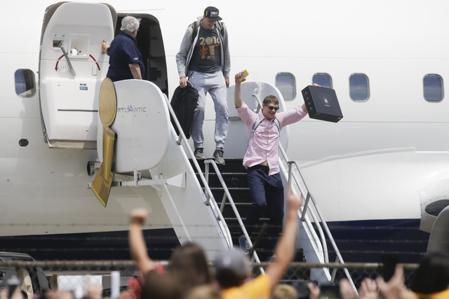 NBA champion Cleveland Cavaliers' Timofey Mozgov, right, celebrates as he arrives at the airport Monday, June 20, 2016, in Cleveland. (John Minchillo/AP)